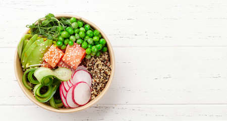 Poke bowl with salmon, avocado and cucumber. Traditional hawaiian meal. Top view flat lay with copy space