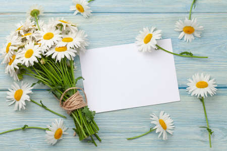 Garden camomile flowers bouquet on wooden table and greering card template. Top view flat lay with copy space Standard-Bild