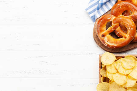 Fresh baked homemade pretzel with sea salt and potato chips on wooden table. Classic beer snack. Top view flat lay with copy space Standard-Bild