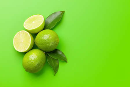 Fresh ripe lime fruits on green background. Top view flat lay with copy space