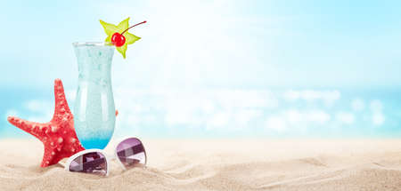 Fresh cold cocktail on tropical beach with palms and bright sand. Summer sea vacation and travel concept with copy space Standard-Bild