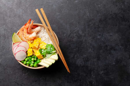 Poke bowl with shrimps, avocado and mango. Traditional hawaiian meal. Top view flat lay with copy space