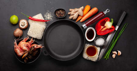 Ingredients for wok cooking with stir fried noodles, shrimps and vegetables on stone background. Top view flat lay with copy space