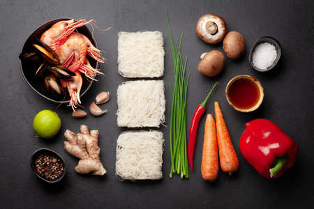 Ingredients for wok cooking with stir fried noodles, shrimps and vegetables on stone background. Top view flat lay Standard-Bild