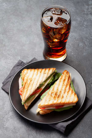 Club sandwich and glass of cola drink with ice. Fast food take away