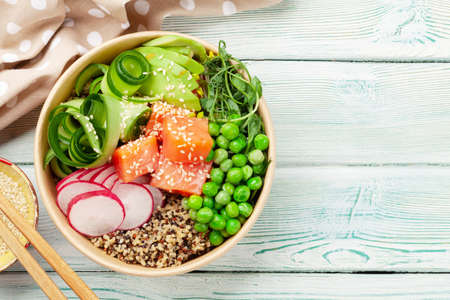 Poke bowl with salmon, cucumber and avocado. Traditional hawaiian meal. Top view flat lay with copy space