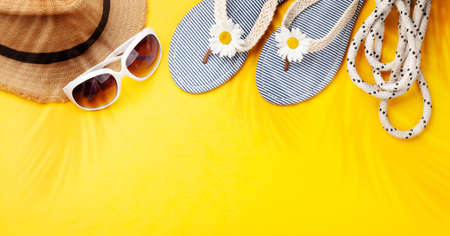 Summer vacation items and accessories. Flip flops, sunglasses and sun hat on yellow background. Top view flat lay with copy space Standard-Bild