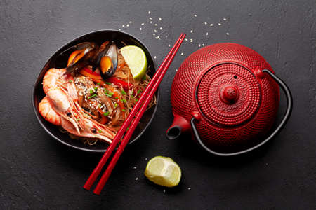 Wok with stir fried noodles, shrimps and vegetables on stone background and teapot. Top view flat lay