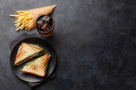 Club sandwich, potato fries chips and glass of cola drink with ice. Fast food take away. Top view with copy space
