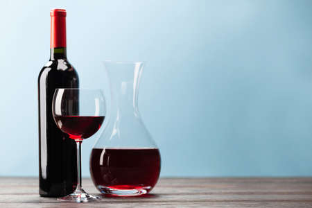 Wine bottle with red wine, wineglass and decanter on wooden table in front of blue background with copy space