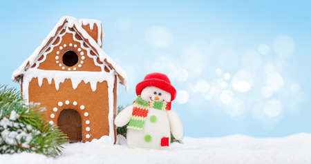 Christmas greeting card with gingerbread house, fir tree and snowman toy. With copy space for your greetings