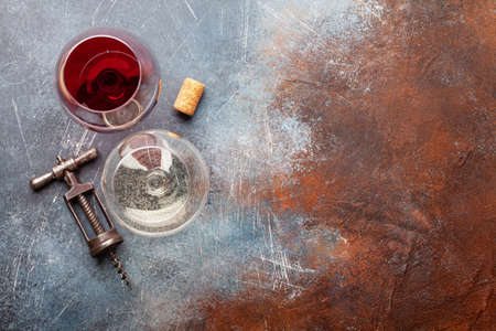 White and red wine glasses and vintage corkscrew on old stone table with copy space. Top view flat lay