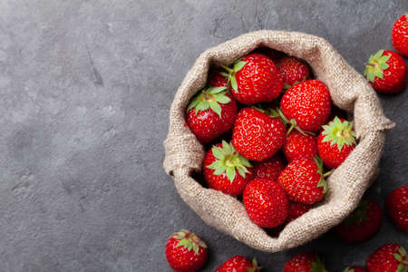 Strawberry in burlap bag. Ripe garden berries on stone table. Top view flat lay with copy space Фото со стока