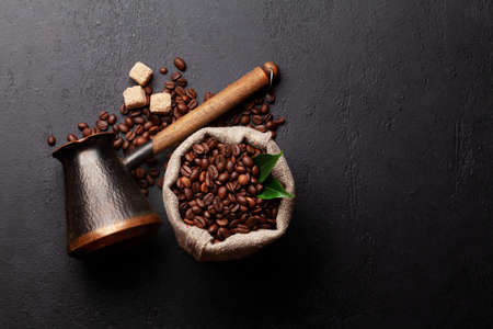 Roasted coffee beans, Turkish jezve and brown sugar. Top view flat lay with copy space