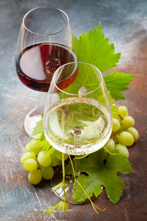 White and red wine glasses and grape on old stone table Фото со стока