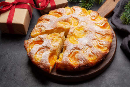 Citrus dessert holiday cake, tangerines and christmas gift boxes