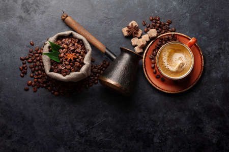 Roasted coffee beans, Turkish jezve, espresso coffee cup and brown sugar. Top view flat lay with copy space Фото со стока