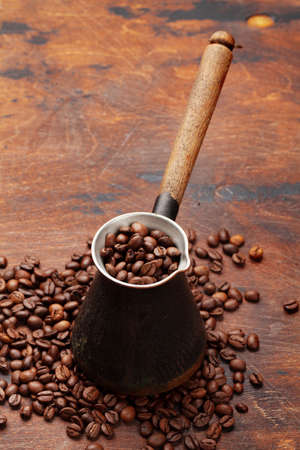 Roasted coffee beans and Turkish jezve on wooden table