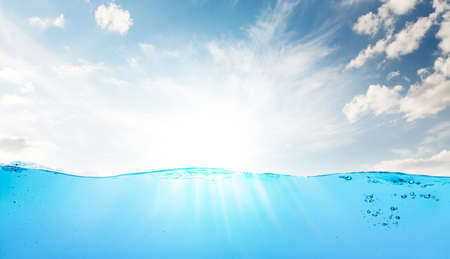 Waterline with sea underwater and blue sunny sky with clouds Фото со стока