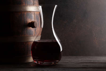 Decanter with red wine and old wooden barrel with copy space