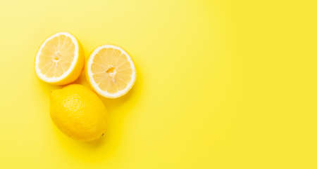 Fresh ripe lemons on yellow background. Top view flat lay with copy space