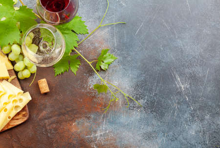 White and red wine glasses, grape and appetizer board with cheese. With copy space. Top view flat lay