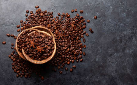 Roasted coffee beans in wooden bowl. Top view flat lay with copy space