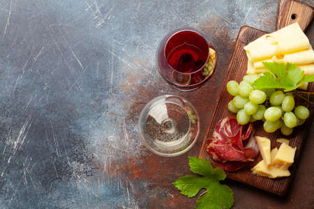 White and red wine glasses, grape and appetizer board with cheese and prosciutto. With copy space. Top view flat lay Фото со стока
