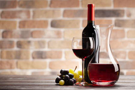 Wine decanter, bottle, glass of red wine and grapes. With copy space