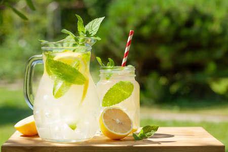 Fresh homemade lemonade with lemon and mint. Outdoor garden table on sunny day Фото со стока