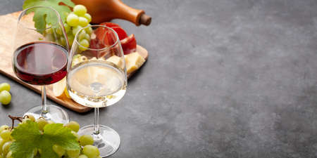White and red wine glasses, grape and appetizer board with cheese and prosciutto. With copy space Фото со стока