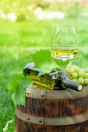 Wine bottle, glass with white wine and grape on old barrel