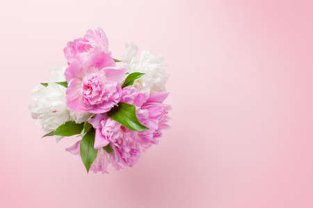 Beautiful garden peony flowers bouquet on pink background. Top view flat lay with space for your holiday greetings