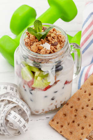 Healthy breakfast with jar of granola, yogurt and fresh berries. Fitness protein meal. Dumbbells and tape measure. Diet concept Фото со стока
