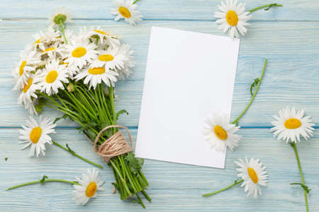 Garden camomile flowers bouquet and greeting card on blue wooden table. Top view flat lay with copy space