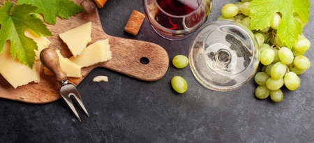 White and red wine glasses, grape and appetizer board with cheese. Top view flat lay Фото со стока