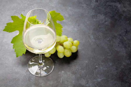 White wine glass and grape on old stone table with copy space