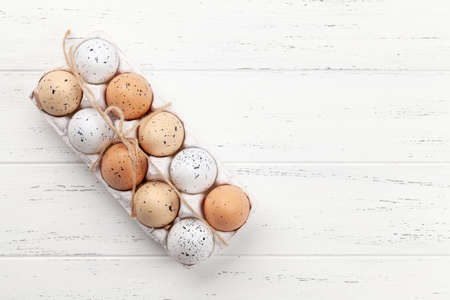 Chicken eggs pack on wooden table. Easter eggs. Top view flat lay with copy space Фото со стока