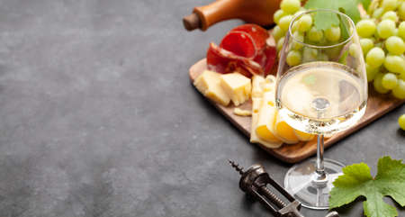White wine glass, grape and appetizer board with cheese and prosciutto. With copy space Фото со стока