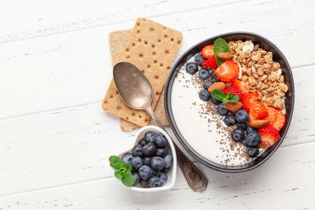 Healthy breakfast with bowl of granola, yogurt and fresh berries. Fitness protein meal. Top view flat lay with copy space Фото со стока