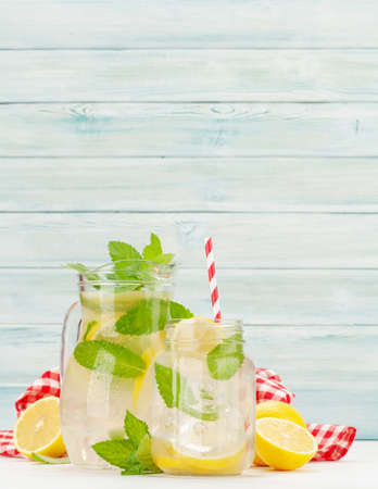 Fresh homemade lemonade with lemon and mint in pitcher and glass jar