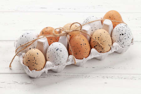 Chicken eggs pack on wooden table. Easter eggs Фото со стока
