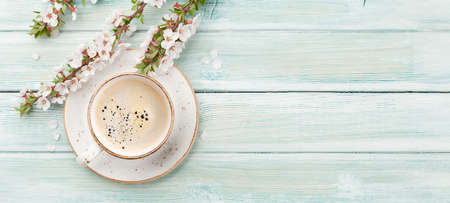 Morning espresso coffee cup on wooden table and cherry blossom. Top view flat lay with copy space Фото со стока