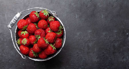 Strawberry in bucket. Ripe garden berries on stone table. Top view flat lay with copy space