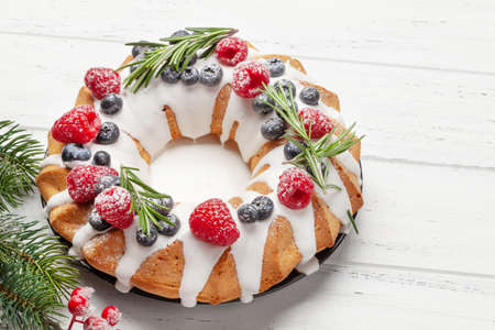 Christmas cake with berries and fir tree on wooden table Standard-Bild