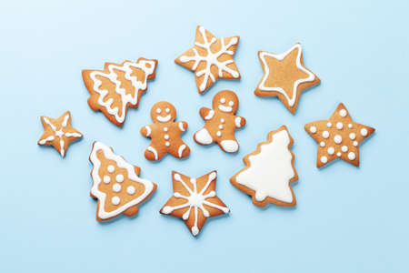 Christmas card with gingerbread cookies over blue background. Top view flat lay Standard-Bild