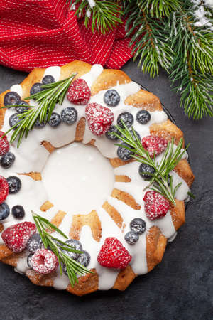 Christmas cake with berries and fir tree. Top view flat lay