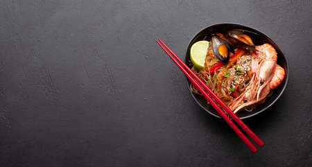 Wok with stir fried noodles, shrimps and vegetables on stone background. Top view flat lay with copy space