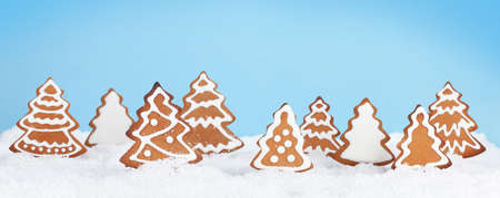 Christmas greeting card with homemade gingerbread trees in snow