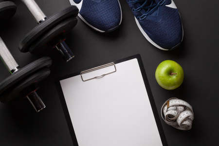 Sneakers, apple and dumbbells. Sport, fitness and healthy lifestyle background. Top view flat lay with copy space